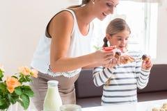 与她的女儿的怀孕的母亲烘烤杯形蛋糕 免版税库存图片