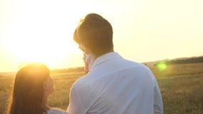 与她的女儿的爸爸和妈妈步行她的在日落的胳膊的 家庭走与孩子在日落 有女儿的父亲 股票录像
