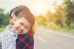与她的妈妈的小的逗人喜爱的亚洲男孩拥抱和微笑对照相机机会 免版税库存照片