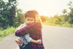 与她的妈妈的小的逗人喜爱的亚洲男孩拥抱和微笑对照相机机会 库存图片