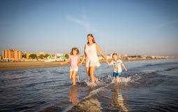 与她的孩子的美好的妈妈戏剧在海 免版税库存图片
