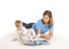 与她的小女儿的新母亲阅读书 免版税库存照片
