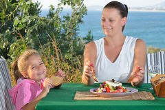 与她的小孩女孩吃午餐的tradiotional地中海沙拉 库存照片