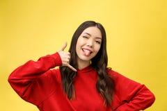 与她的手指的俏丽的年轻女人陈列电话标志 五颜六色的演播室画象有黄色背景 免版税库存照片