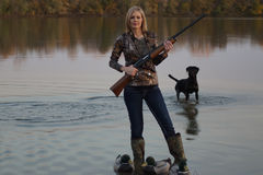 与她的拉布拉多猎犬的女性鸭子猎人 免版税库存图片