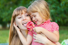 与她的母亲棒棒糖的小女孩份额 免版税图库摄影