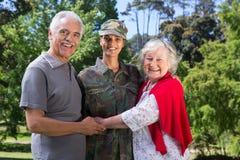 与她的父母团聚的战士 库存照片