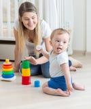 与她的男婴的微笑的母亲聚集的玩具金字塔 免版税库存图片