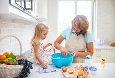 与她的祖母的逗人喜爱的小女孩烘烤 库存照片