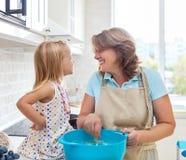 与她的祖母的逗人喜爱的小女孩烘烤 免版税库存照片