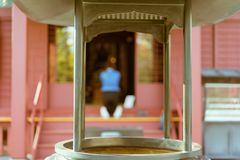 与她的膝盖的祈祷在背景中的妇女的佛教熏香台在著名Senso籍寺庙在浅草,东京,日本 库存照片