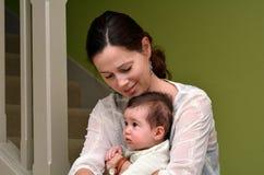 与她的婴孩的年轻母亲戏剧在家 免版税库存照片