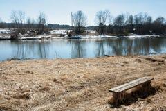 与她的阴影的老长木凳在春天海岸Ne的干草 免版税库存图片