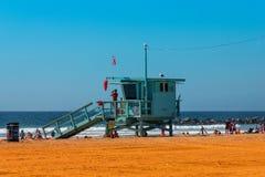 与妇女救生员的救生员塔当班在海滩圣塔蒙尼卡 与五颜六色的天空和海滩的Baywatch塔 库存照片