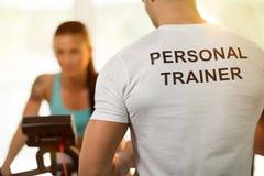 与妇女的个人教练员在健身房的循环的机器的 免版税库存图片