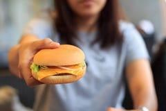 与妇女的乳酪汉堡选择焦点和迷离背景,特写镜头乳酪汉堡 库存图片