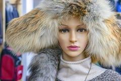 与妇女的裘皮帽的时装模特在服装店 图库摄影