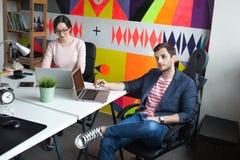 与妇女的年轻男性谈论的事务在现代办公室 库存照片