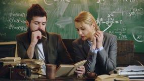 与妇女秘书的商人工作在学校办公室 有胡子的男人和肉欲的妇女读了书 加上打字机 股票录像