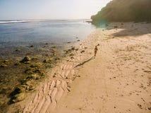 与妇女赛跑的美丽的热带海滩 图库摄影