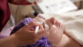 与妇女面膜的防皱面孔治疗 美容师在与刷子的面孔上把一个润湿的胶凝体放 A 股票录像