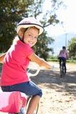 与妈妈的女孩微笑的骑马自行车 库存图片
