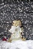 与姜饼圣诞节天使星状装饰的降雪在雪堆反对木背景的 库存图片