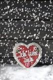 与姜饼心脏的降雪在雪堆反对木背景的 库存图片