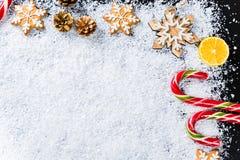 与姜饼雪花、白色雪、玩具、柠檬、糖果和新年装饰的圣诞节背景 寒假框架 库存照片