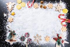 与姜饼雪花、白色雪、玩具、柠檬、糖果和新年装饰的圣诞节背景 寒假框架 免版税库存照片