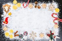 与姜饼雪花、白色雪、玩具、柠檬、糖果和新年装饰的圣诞节背景 寒假框架 库存图片