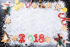与姜饼雪花的圣诞节背景和2018年,白色雪、玩具、柠檬、糖果和新年装饰 寒假框架 库存照片