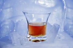 与威士忌酒颜色强的酒精饮料的玻璃在残破的蓝色冰站立 库存照片