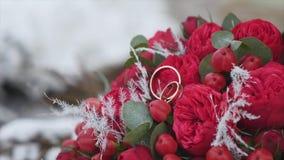 与婚戒的婚礼花束与在雪背景的红色花  股票录像
