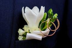 与婚戒的新郎的美丽的钮扣眼上插的花 免版税库存照片