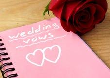 与婚礼誓约的桃红色笔记薄和上升了 库存照片