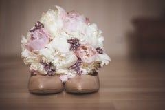 与婚礼鞋子的美丽的新娘花束 库存图片