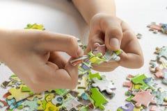 与婴孩把柄,有色的玩具难题的儿童的手的难题 免版税图库摄影