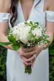 与婴孩的呼吸的美丽的白色玫瑰色花束由有佩带一白色婚纱和订婚rin的黑发的一个新娘举行了 库存照片