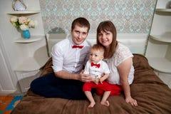 与婴孩的家庭在屋子里 一起妈妈、爸爸和儿子 免版税图库摄影