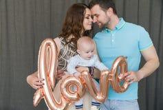 与婴孩的愉快的年轻可爱的家庭 免版税图库摄影