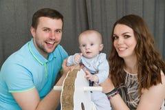 与婴孩的愉快的年轻可爱的家庭 免版税库存照片