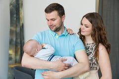 与婴孩的愉快的年轻可爱的家庭 图库摄影