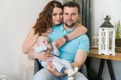 与婴孩的愉快的年轻可爱的家庭 库存图片