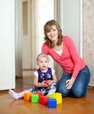 与婴孩的母亲作用在家 图库摄影