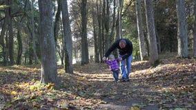 与婴孩的父亲步行在秋天公园 父权,童年 4K 股票录像