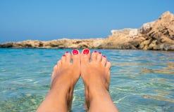 与嬉戏的面带笑容的修脚 在天蓝色的海水的女性脚 免版税库存图片