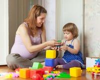 与子项的愉快的怀孕的母亲作用 免版税库存照片