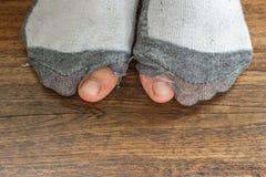 与孔和脚趾的穿的袜子。 免版税库存照片
