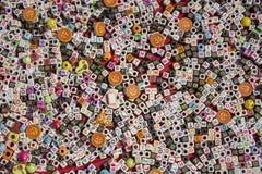 与孔和英语字母表谎言的多彩多姿的信件的一个白色和黑立方体在一块红色布料的堆 库存照片